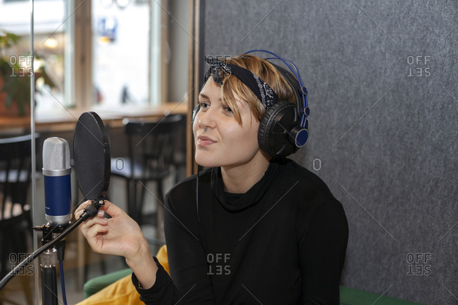 Woman wearing headphones and sitting at table with microphone