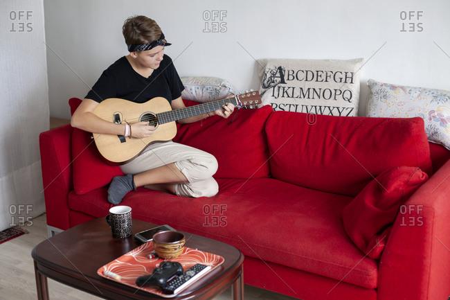 Young woman playing guitar on sofa