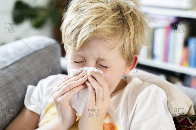 Boy with cold at home, sneezes