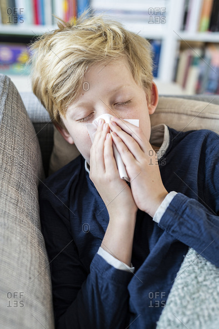 Boy with cold sneezing at home