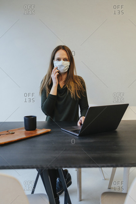 Woman wearing protective mask in office