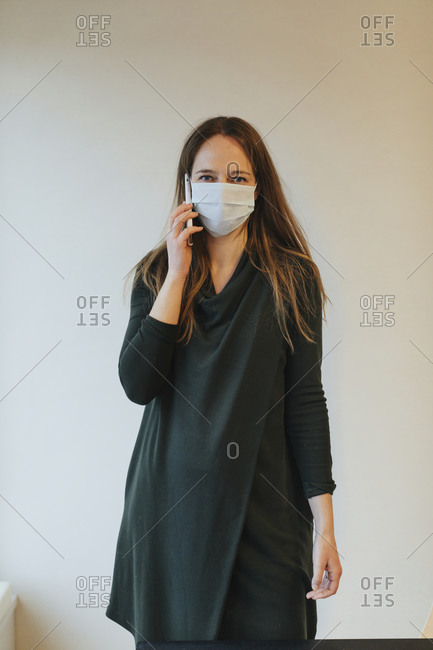 Woman wearing protective mask on the phone