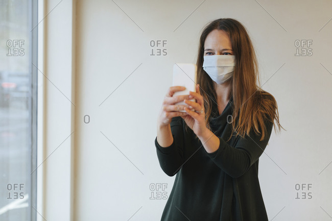 Woman wearing protective mask while taking selfie