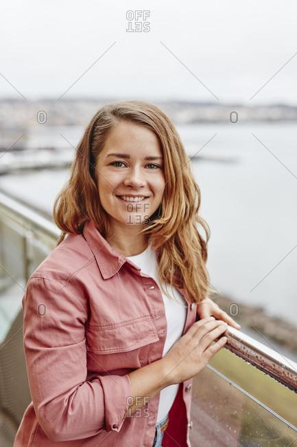 Woman on balcony looking at camera