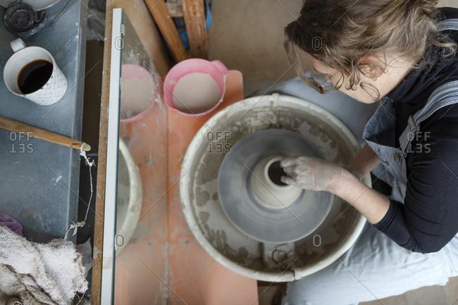 Woman using potters wheel in studio