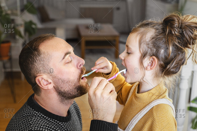 Father and daughter brushing each other teeth