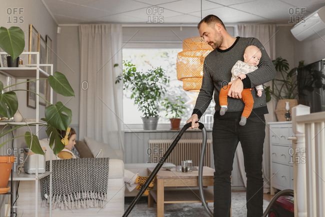 Father carrying baby while vacuum cleaning