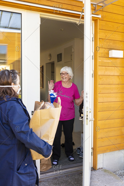 Woman delivering shopping to senior woman
