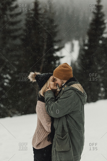 Young couple kissing on a snowy day