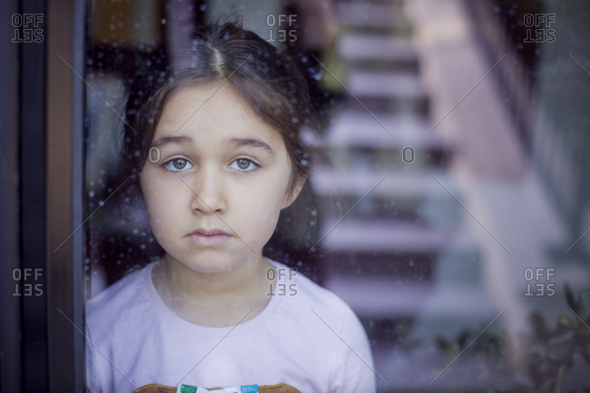 Sad girl looking through glass door