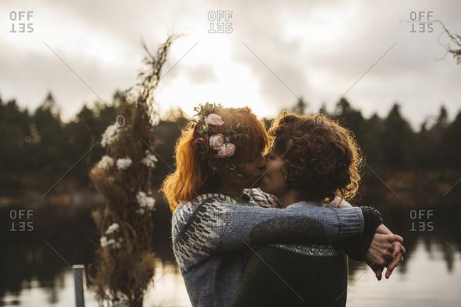 Lesbian couple kissing at lakeshore