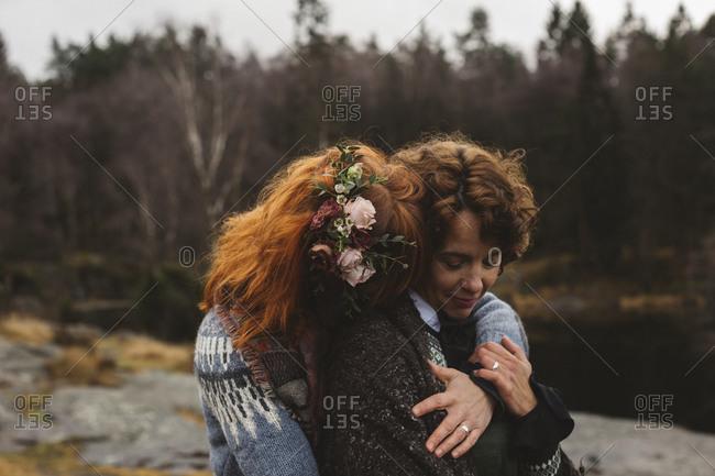 Lesbian couple embracing at lakeshore