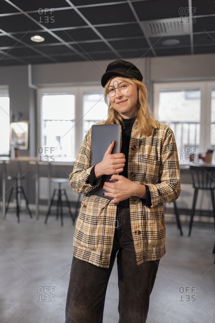 Smiling woman standing in office and looking at camera