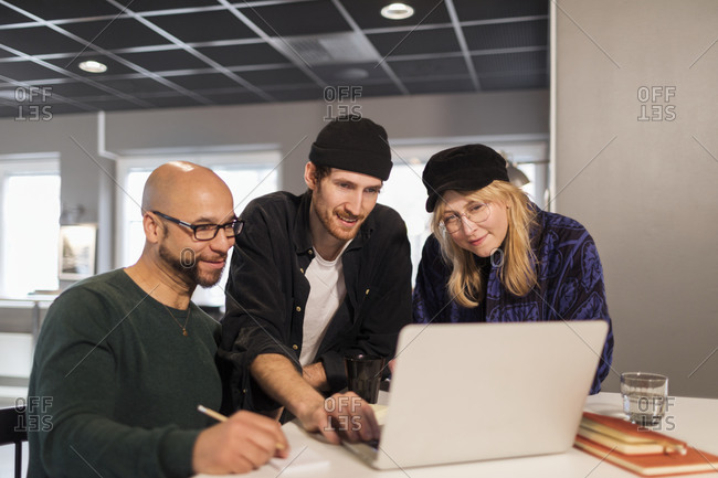 Coworkers in office looking at laptop