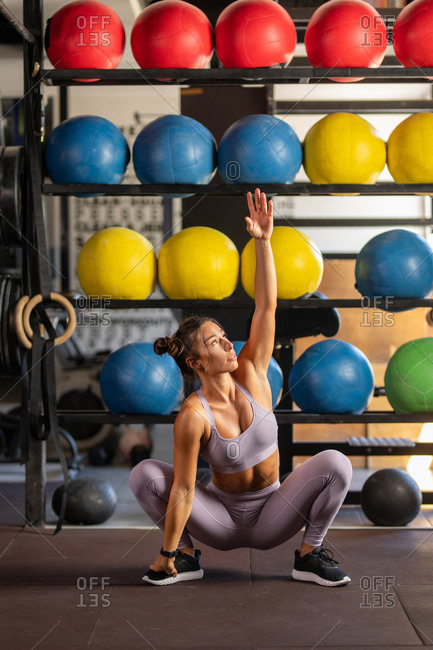Woman exercising squat with reach at the gym