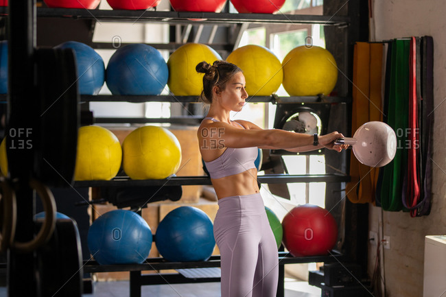 Female athlete exercising with kettle bell in gym