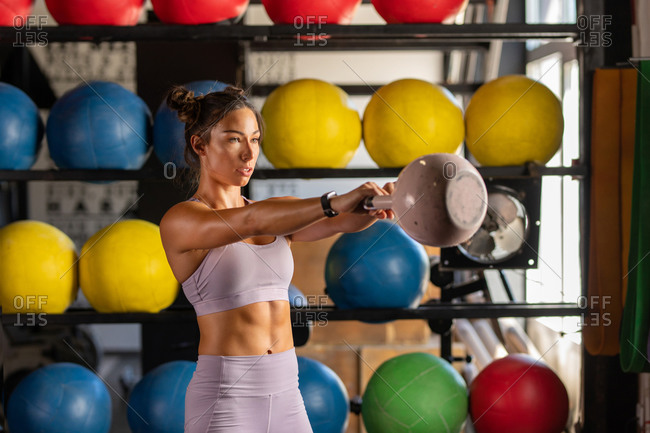 Beautiful woman lifting kettle bell at the gym
