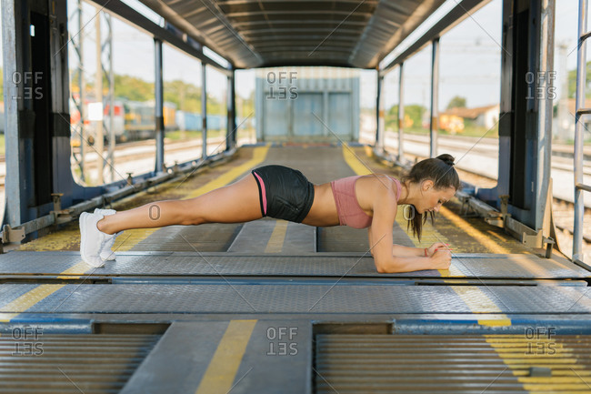 Young woman doing a plank outdoors
