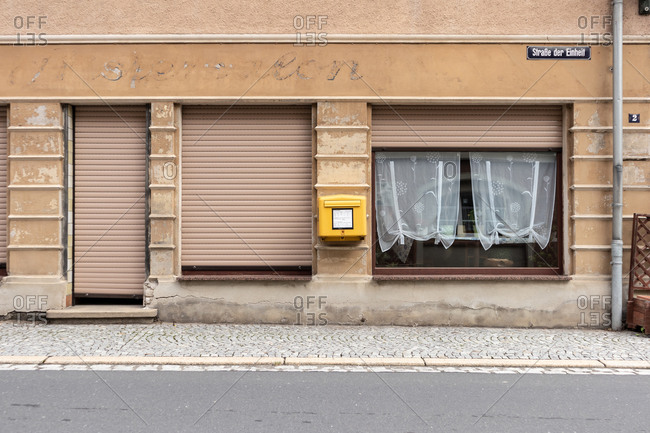 Saxony, Germany - September 3, 2020: Old closed down storefront with yellow mailbox on wall