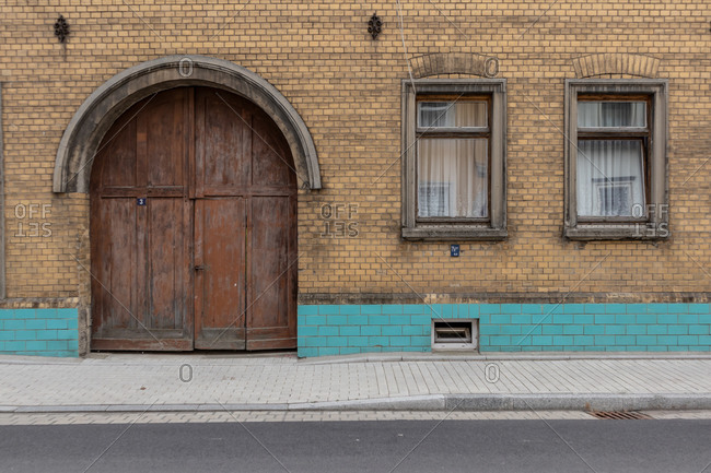 Old brick building exterior with large arched wooden doors in Saxony, Germany