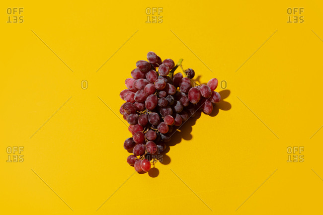 Red grape on yellow background
