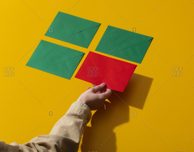 Woman hand holds red envelopes near green ones on yellow background