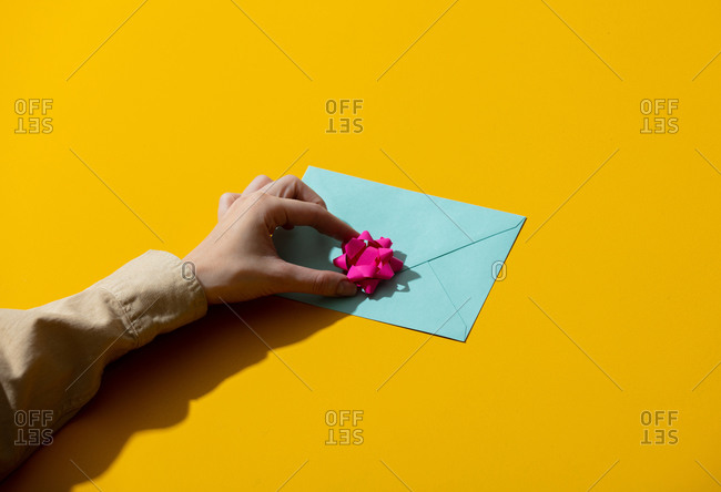 Female hand and blue envelope with gift bow on yellow background
