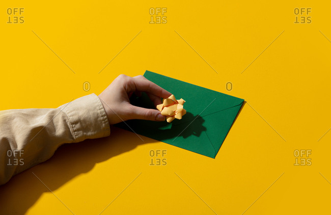 Female hand putting a bow on green envelope on yellow background