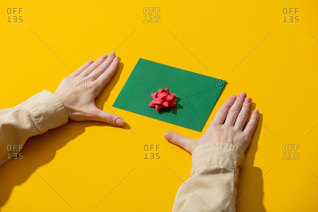 Female hand and green envelope with gift bow on yellow background