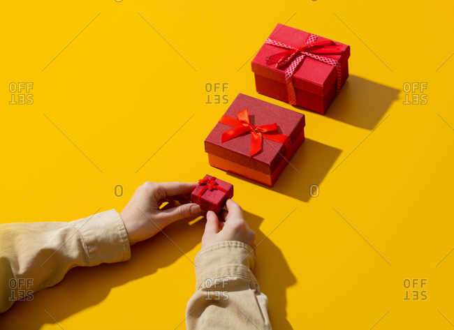 Female holds gift box on yellow background with other boxes