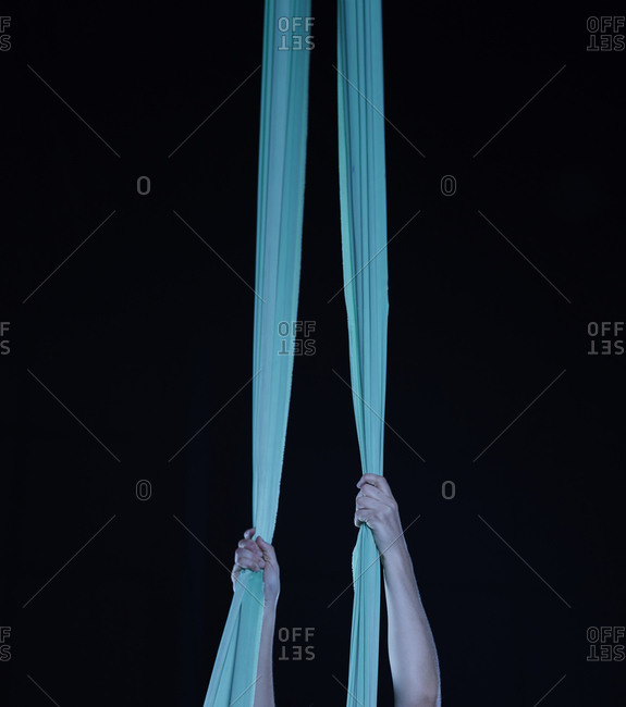 Woman's hands hanging onto two blue silk cloths