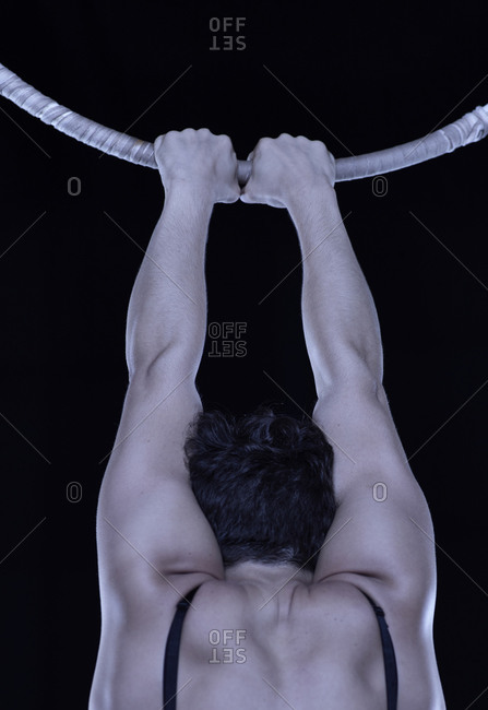 Male acrobats hanging from a large hoop