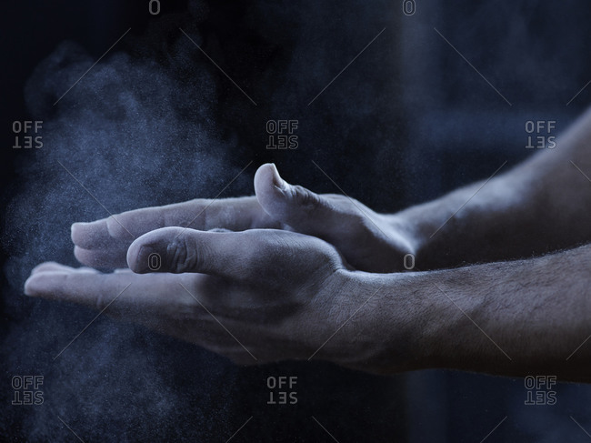 Male acrobats using chalk powder on hands close up