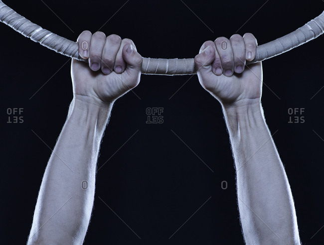 Acrobat's hands hanging from a large hoop