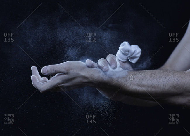 Male acrobats using chalk powder on hands and arms