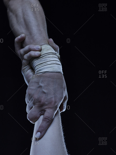 Two acrobats holding each other's wrapped wrists