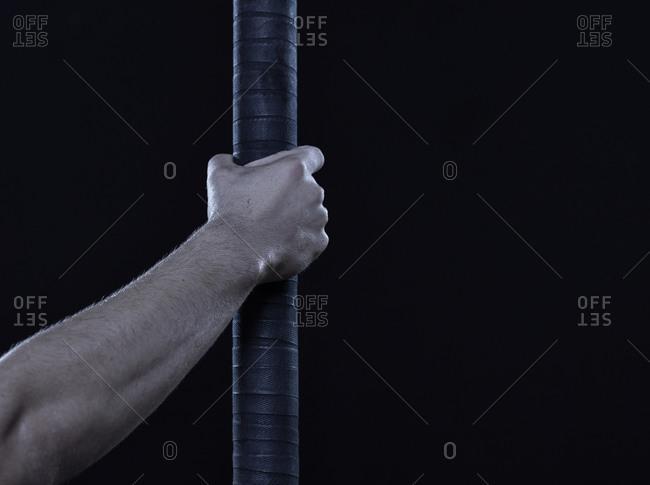Acrobat's hand around a pole in front of dark background