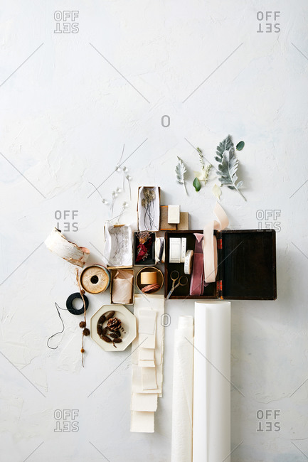 Overhead view of natural crafting items in boxes by paper on white surface