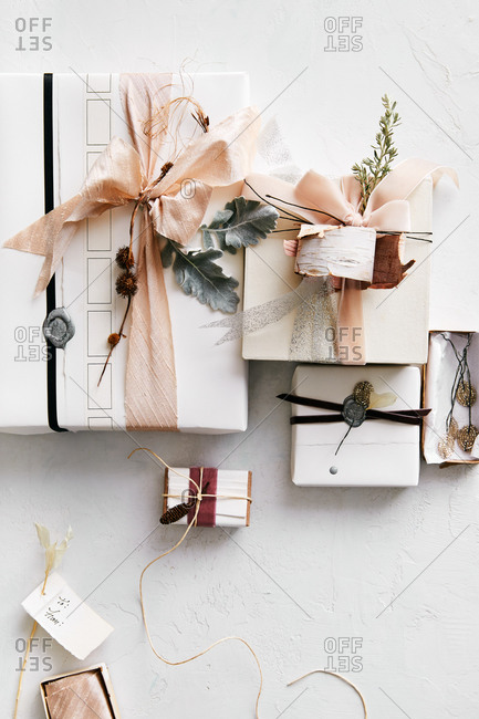 Gifts wrapped in white paper and decorated with natural elements on white surface