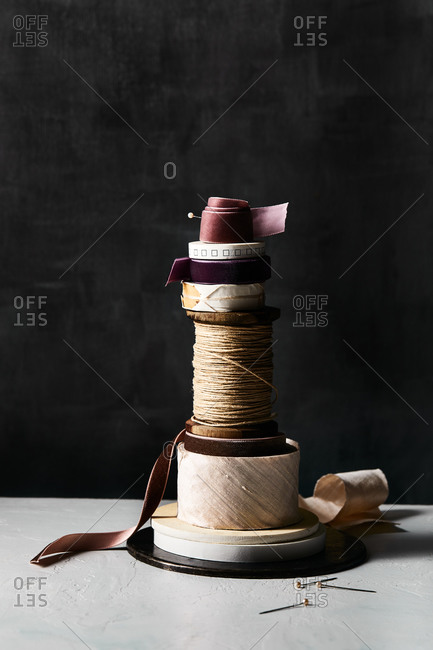 Stack of ribbon and string in front of black background