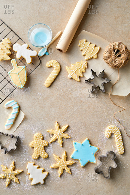Christmas cookies being iced on light surface
