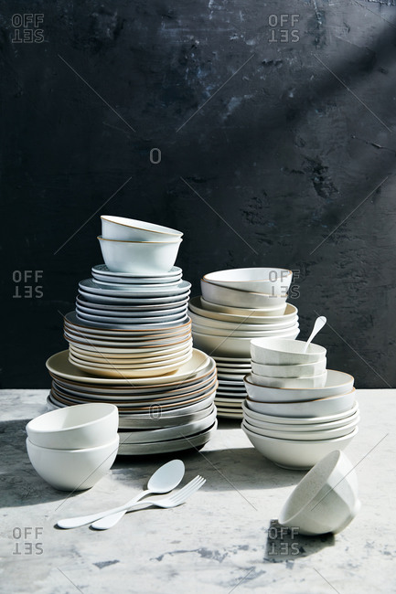 Abundance of dishes stacked on marble surface with black background