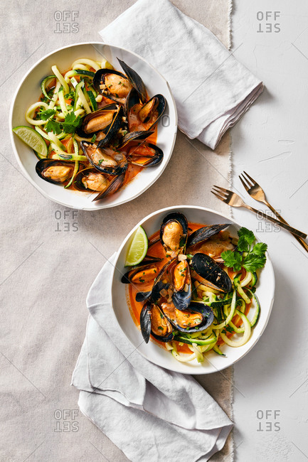 Overhead view of mussels and zucchini noodles served in bowls