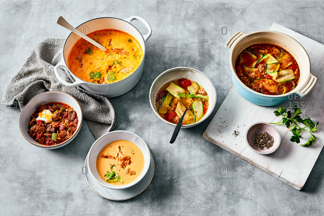 Variety of warm hearty soups on gray background