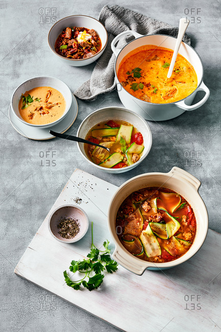 Warm hearty soups on gray background