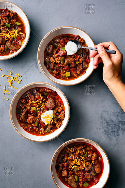 Woman serving bowls of chili with a dollop of sour cream