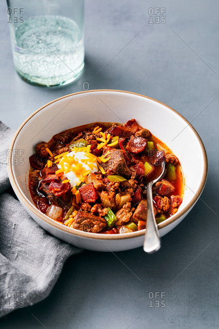 Bowl of chili with a dollop of sour cream and cheese