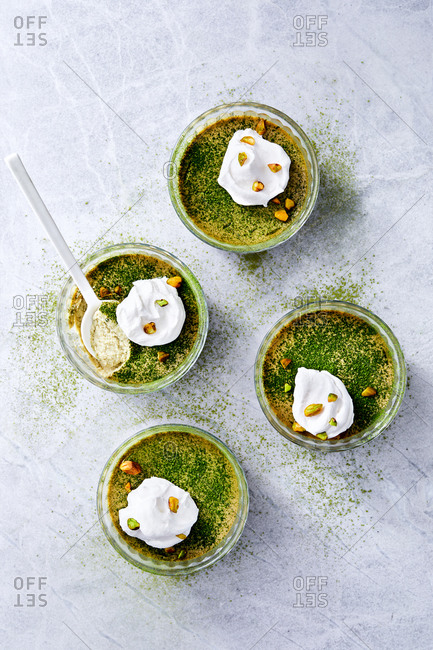 Overhead view of green tea coconut milk custard topped with whipped cream and pistachios