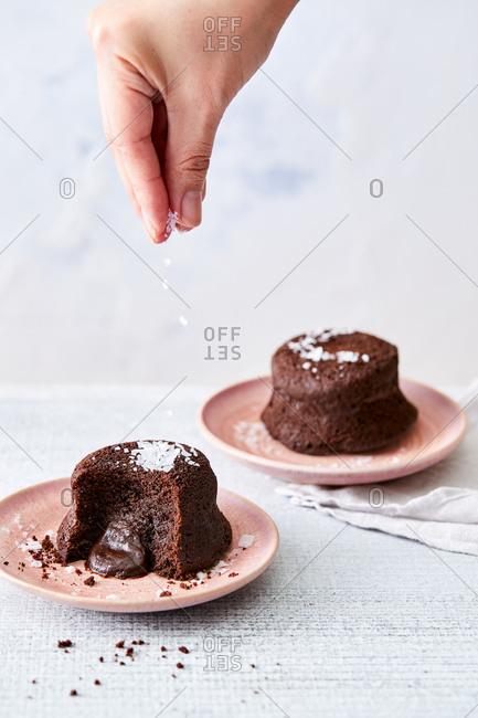 Hand sprinkling sea salt over chocolate lava cakes