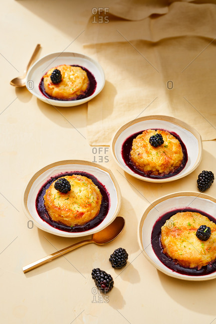 Mini custard cakes topped with blackberries
